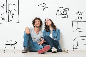 Portrait Of Happy Young Couple Sitting On Floor Looking Up While